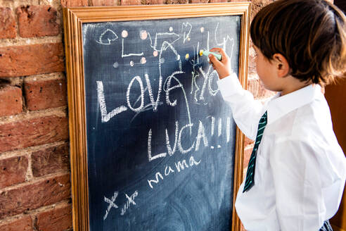 Boy in school uniform writing on blackboard at home - CUF52393