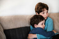 Big brother hugging toddler, staring in disbelief on sofa - CUF52402