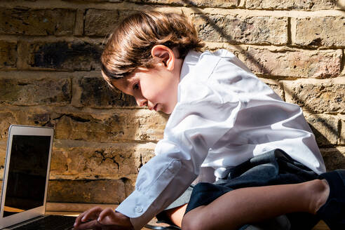 Boy in school uniform using laptop at home - CUF52429