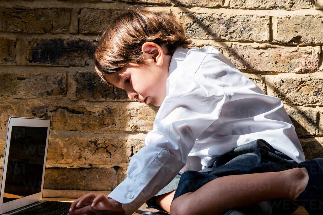 Boy in school uniform using laptop at home - CUF52429 - Bonfanti Diego/Westend61