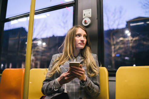 Young woman with long blond hair sitting in train carriage with smartphone at dusk - CUF52435