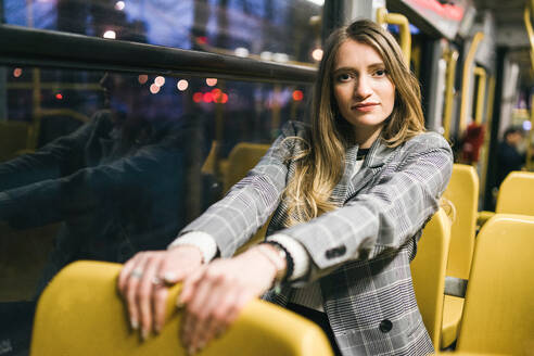 Young woman with long blond hair sitting in train carriage at dusk, portrait - CUF52438