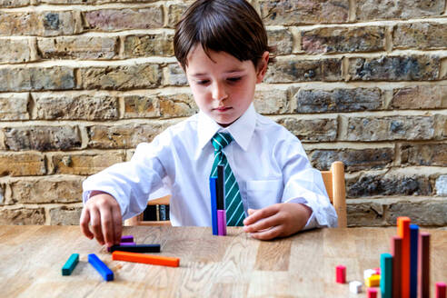 Boy in school uniform playing with colour sticks at home - CUF52441