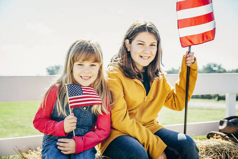Caucasian girls waving American flags on hay ride - BLEF08195