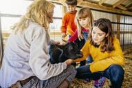 Caucasian children petting goat in barn - BLEF08207