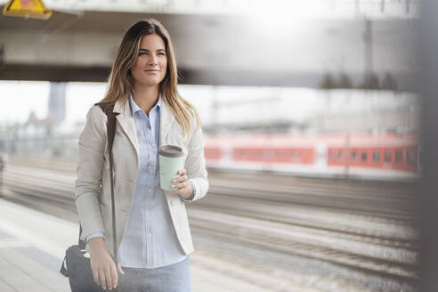 Young businesswoman with coffee to go cup, standing on station - DIGF07144