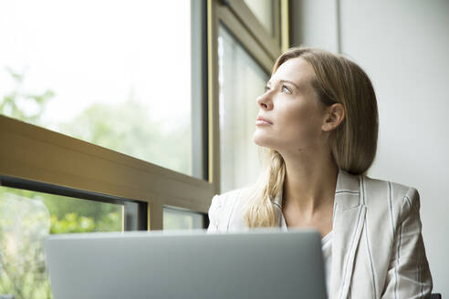 Businesswoman looking out of window - MFRF01326