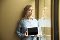 Businesswoman holding tablet looking out of window - MFRF01332