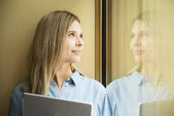 Businesswoman with tablet looking out of window - MFRF01335