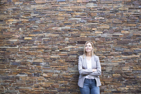 Woman in front of a wall looking upa, arms crossed - MFRF01341