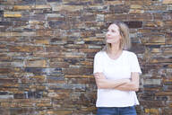Woman in front of a wall looking sideways, arms crossed - MFRF01344