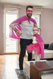Father and daughter playing superhero and superwoman - ZEDF02484