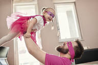 Father and daughter playing superhero and superwoman, pretending to fly - ZEDF02496