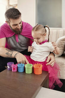 Father and daughter wearing superhero and superwoman costume, playing with stacking cups - ZEDF02499