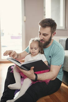 Father and daughter reading a book - ZEDF02514