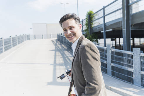 Smiling businessman with E-Scooter - UUF18154