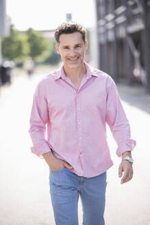 Portrait of businessman, wearing pink shirt - UUF18181