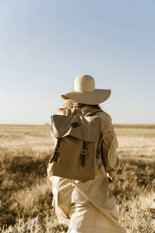 Rear view of female traveller with backpack on meadow - ERRF01562
