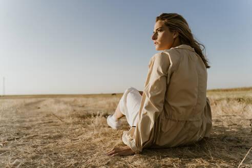 Female traveller sitting on dry meadow, looking sideways - ERRF01598