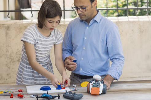 Father teaching his daughter electronics and robotics - ALBF00928