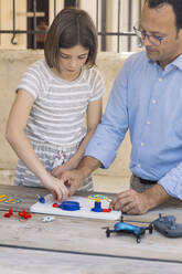 Father teaching his daughter electronics and robotics - ALBF00931
