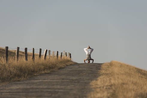 Mid distance view of mature man doing headstand on road against clear sky - KJF00321