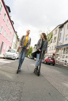 Young women riding electric scooters in the street - JOSF03321