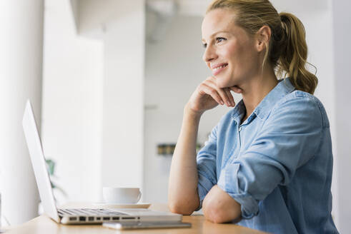 Blond woman sitting in coffee shop, using laptop - JOSF03345