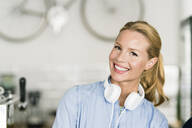 Blond woman in coffee shop with headphones - JOSF03384