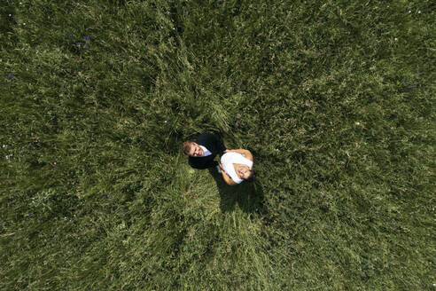 Aerial view of pregnant bride with her husband on a meadow - HMEF00482