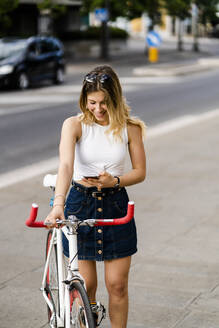 Smiling young woman with racing cycle looking at cell phone - GIOF06562