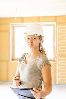 Portrait of a confident young woman in a new wooden house - TCF06131