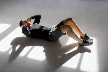 Athlete doing crunshes in sunlit studio - MAUF02622