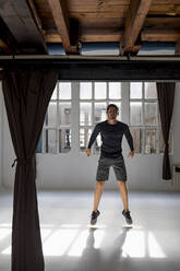 Dynamic athlete jumping in studio loft - MAUF02628