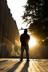 Back view of skater standing at backlight with skateboard on his head - AFVF03563