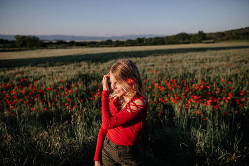 Little girl standing by poppy field - OGF00007