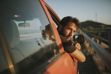 Man on a road trip looking out of car window - DMGF00076