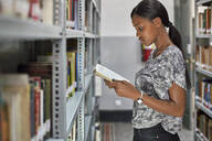 Young woman checking a book at bookshelf at National library, Maputo, Mocambique - VEGF00389