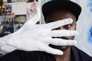 Black artist through fingers of white painted hand at his studio - IGGF01248