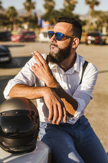 Portrait of bearded motorcyclist with mirrored sunglasses leaning on his helmet smoking - LJF00293