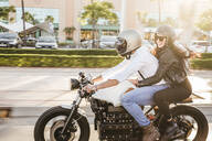 Couple riding motorbike in the city - LJF00296