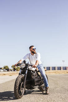 Portrait of bearded man sitting on his motorbike - LJF00314