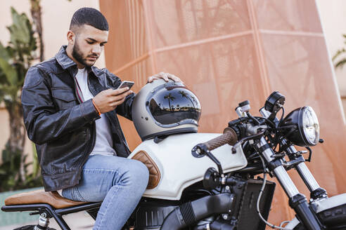 Young man sitting on his motorbike  using cell phone - LJF00326