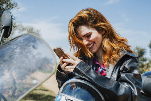 Portrait of happy redheaded woman on motorbike looking at cell phone, Andalusia, Spain - LJF00338