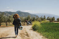 Back view of redheaded motorcyclist walking on dirt track, Andalusia, Spain - LJF00341