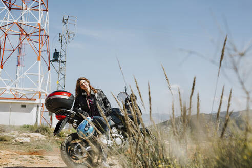Redheaded woman with motorbike in nature - LJF00344
