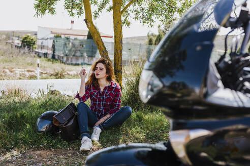 Motorcyclist having cigarette break under a tree - LJF00347