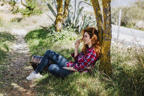Redheaded woman having cigarette break under a tree - LJF00350
