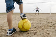 Close-up of man and boy playing soccer on the beach - JRFF03417