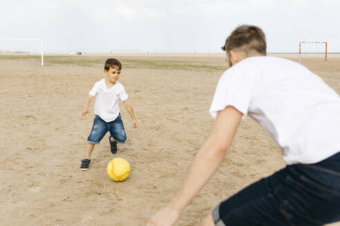 Man and boy playing soccer on the beach - JRFF03420